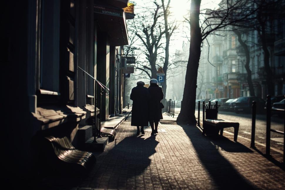 two ladies walking into sunny sidewalk jezyce church sunday morning winter