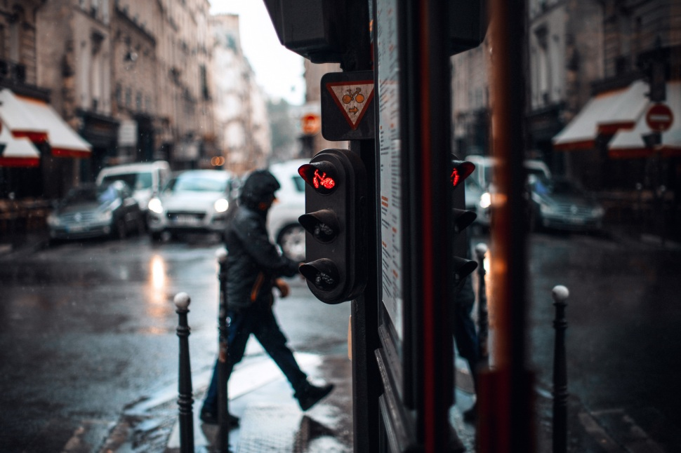 wet rainy day paris red stop sign man crossing street